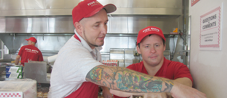 Todd Snowmen, general manager of Five Guys Burgers and Fries, works with Charlie Barba at the location in Palm Bay Road. Charlie has work for Five Guys Bergers & Fries for almost two years and Snowmen is very proud of his work.
