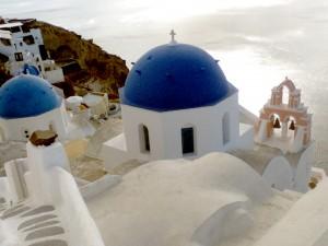 El panorama de iglesias con cúpulas azules y casitas blancas como la nieve es una vista icónica de Santorini.