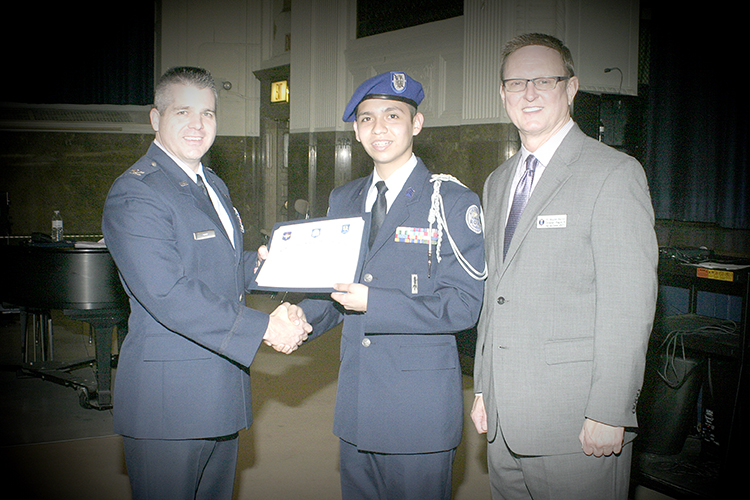 "From left to right: Colonel Woods, National AFJROTC Director, presents the ""Top Performer"" award during the unit evaluation to Cadet Captain Pardey, from Colombia; and Mr. Barron, Regional Director."