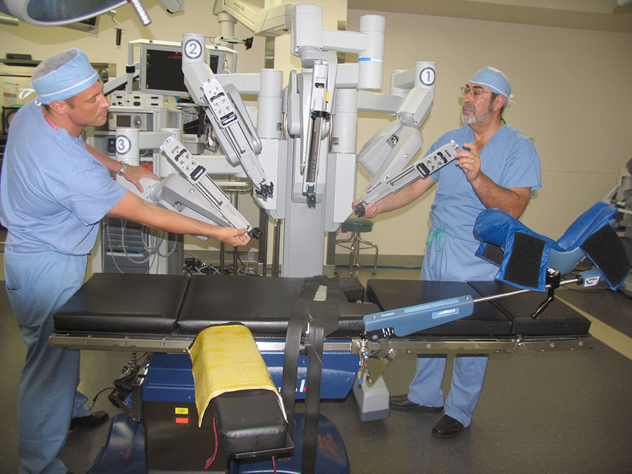 Dr. Edgar Figueroa inspects the surgical robot with da Vinci Clinical Sales Representative Christian Ehret. This robotic equipment utilizes magnified three-dimensional vision and tiny wristed instruments with the ability to bend well beyond the reach of the human wrist.