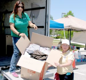 Marcela Irreno, presidente de Servientrega en Melbourne, y Anita Corrente, presidenta de la Ecuadorian American Assosiation of Brevard, cargan un camión de donaciones para los damnificados de Ecuador.
