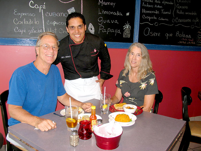 Chef Jorge Morales serves Robert and Suzan Harrison, while enjoying a Cuban sandwich accompanied with delicious empanadas.